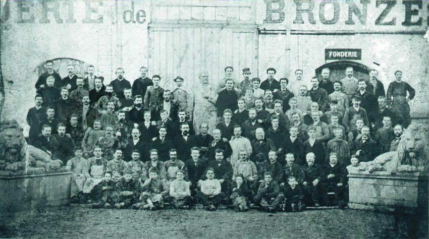 Ancienne photo du personnel de la Compagnie des Bronzes posant devant l'enseigne de la fabrique.