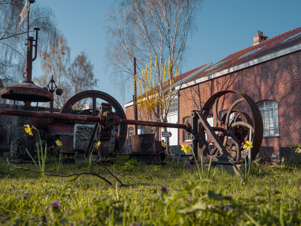 Vue du site avec ses machines exposées en extérieur et le musée en arrière-plan