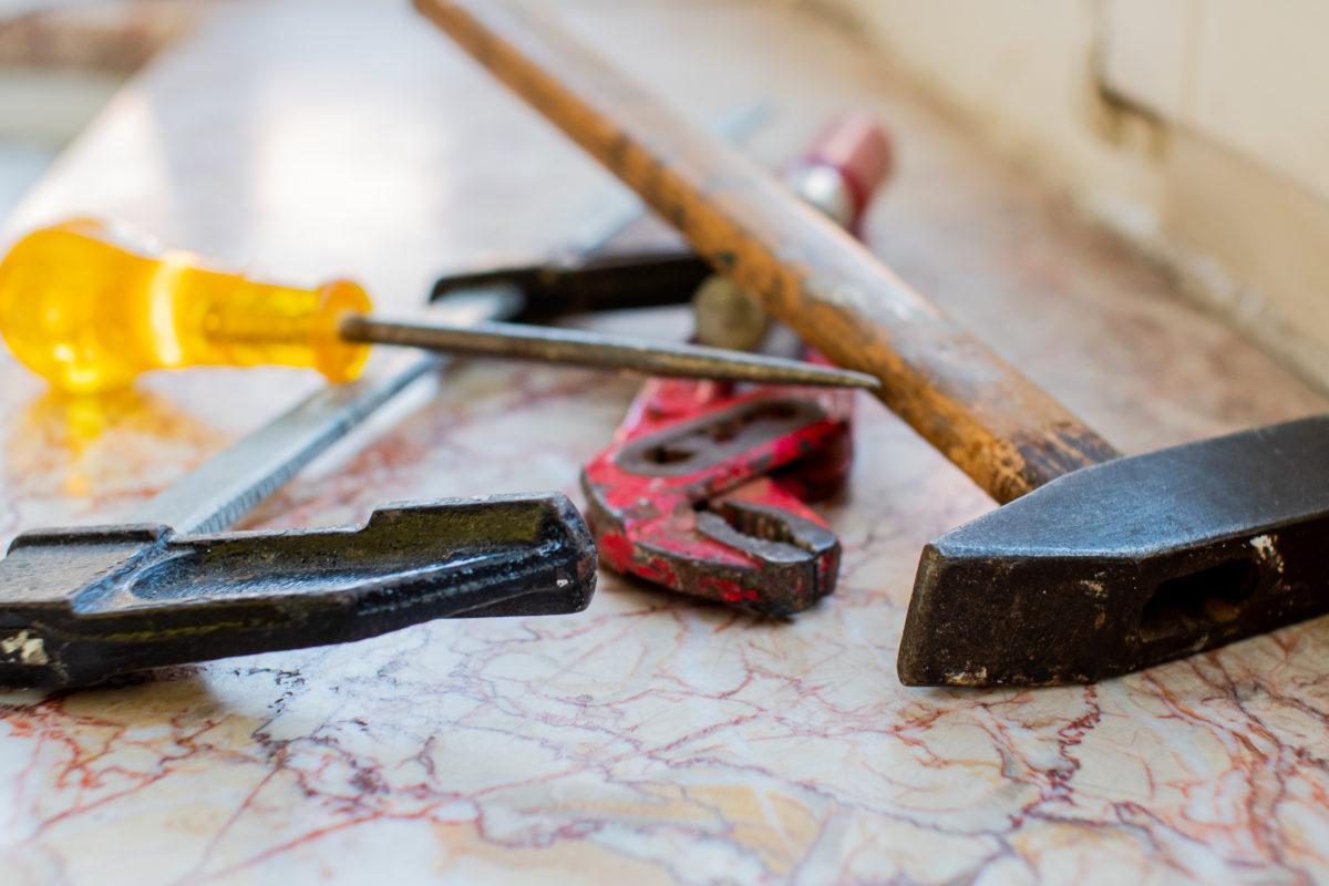 Des outils sont posés sur un plan en marbre. On y voit notamment tournevis, clef anglaise et marteau...