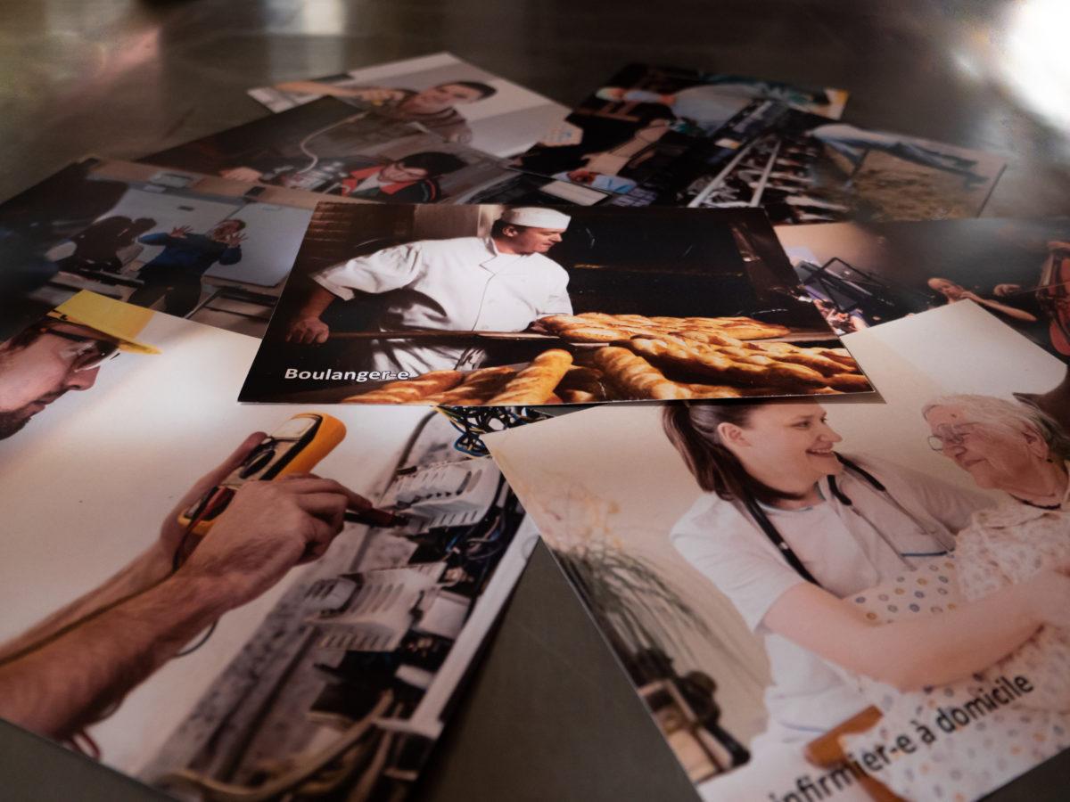 des photos de personnes pratiquant divers métiers sont posés en vrac. On reconnaît entre autres un boulanger, une infirmière, un électricien, un agriculteur