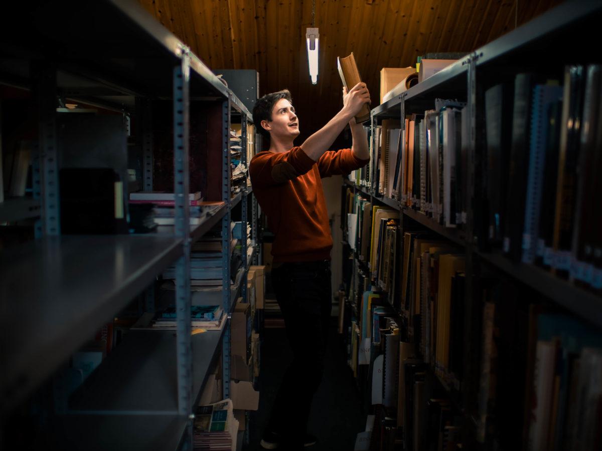 Un jeune homme; debout dans un des rayons du centre de documentation, tient dans ses mains un ouvrage. Son visage resplendit.