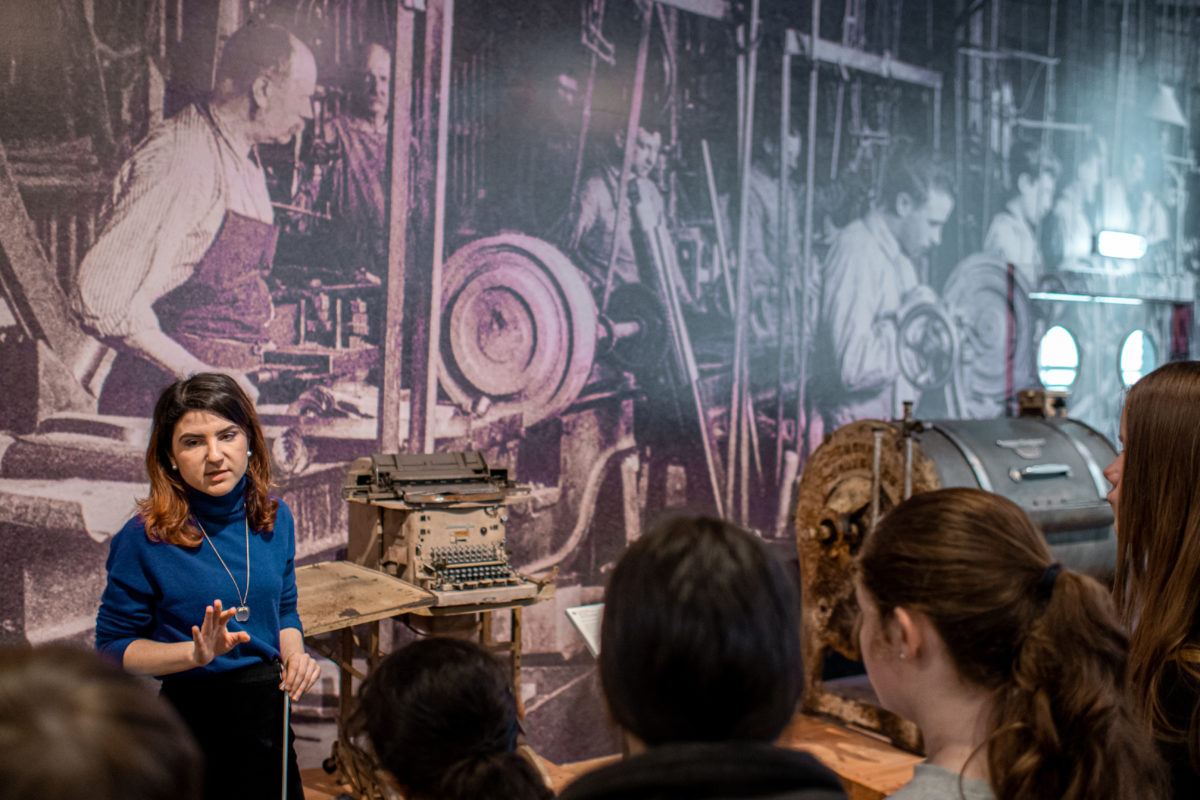 l'animatrice et les jeunes devant une grande bâche murale représentant les conditions de travail d'antan dans l'industrie.
