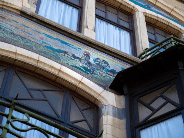 façade d'une maison à l'architecture art nouveau. Elle présente le sgrafitte d'un coq et une balustrade en fer forgé