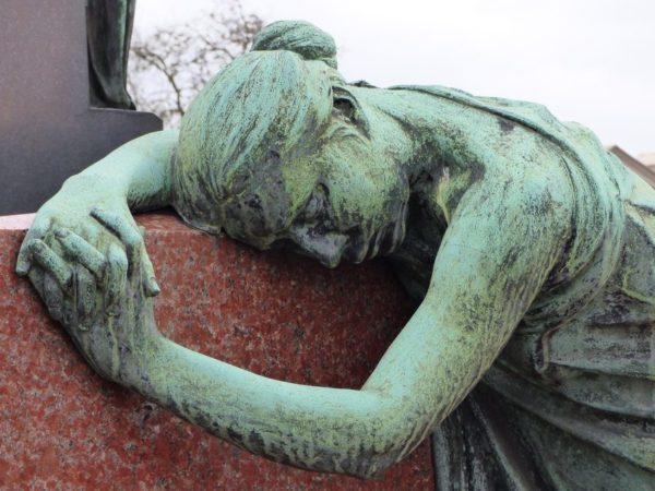 Photo d'une pleureuse en bronze sur une des tombes deu cimetière.