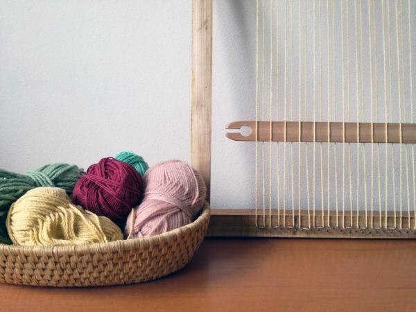 Cadre à tisser et pelottes de fils de couleurs