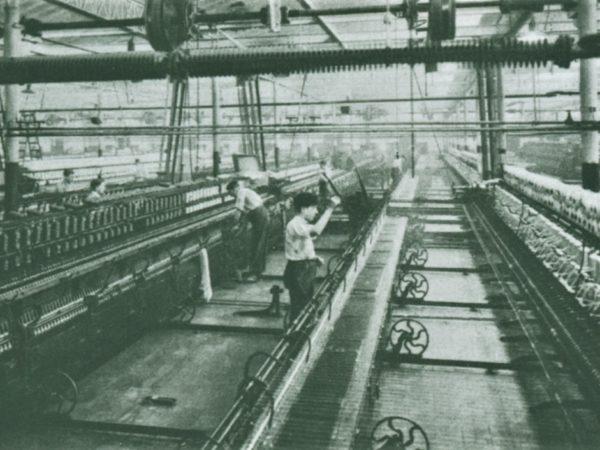Ouvriers travaillant sur des machines dans une usine de filature de laines