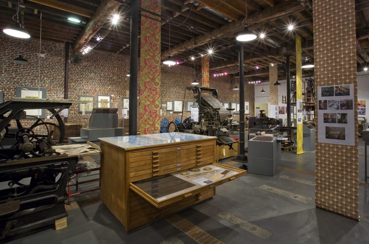exposition présentant machines et papiers peints pendus du plafond