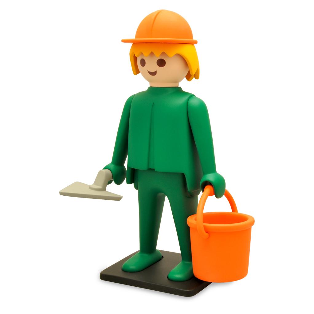Image d'un personnage playmobil, un casque sur la tête et tenant un seau et une truelle