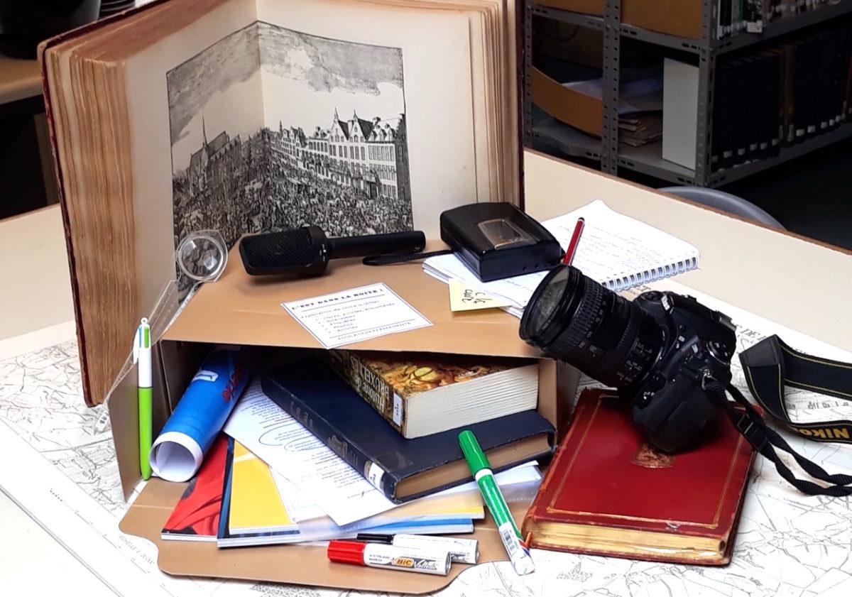 Boîte de centre documentation avec en vrac : livres, revues, brochures, carnet d enotes, bics, loupe, feutres, enregistreur, micro et appareil photo...