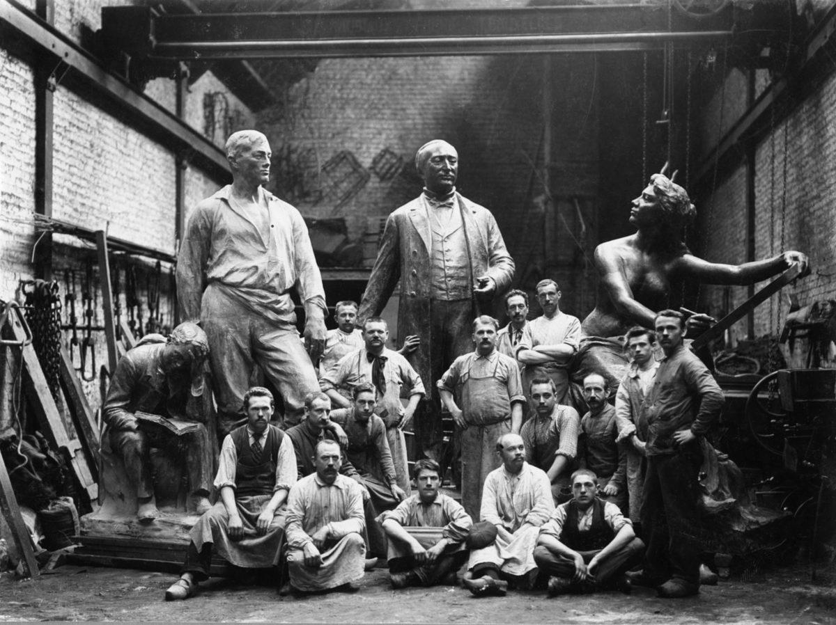 Ancienne photo en noir et blanc datant de 1900. Des ouvriers de la Compagnie des Bronzes posent dans la halle de montage devant trois grandes statues en bronze.