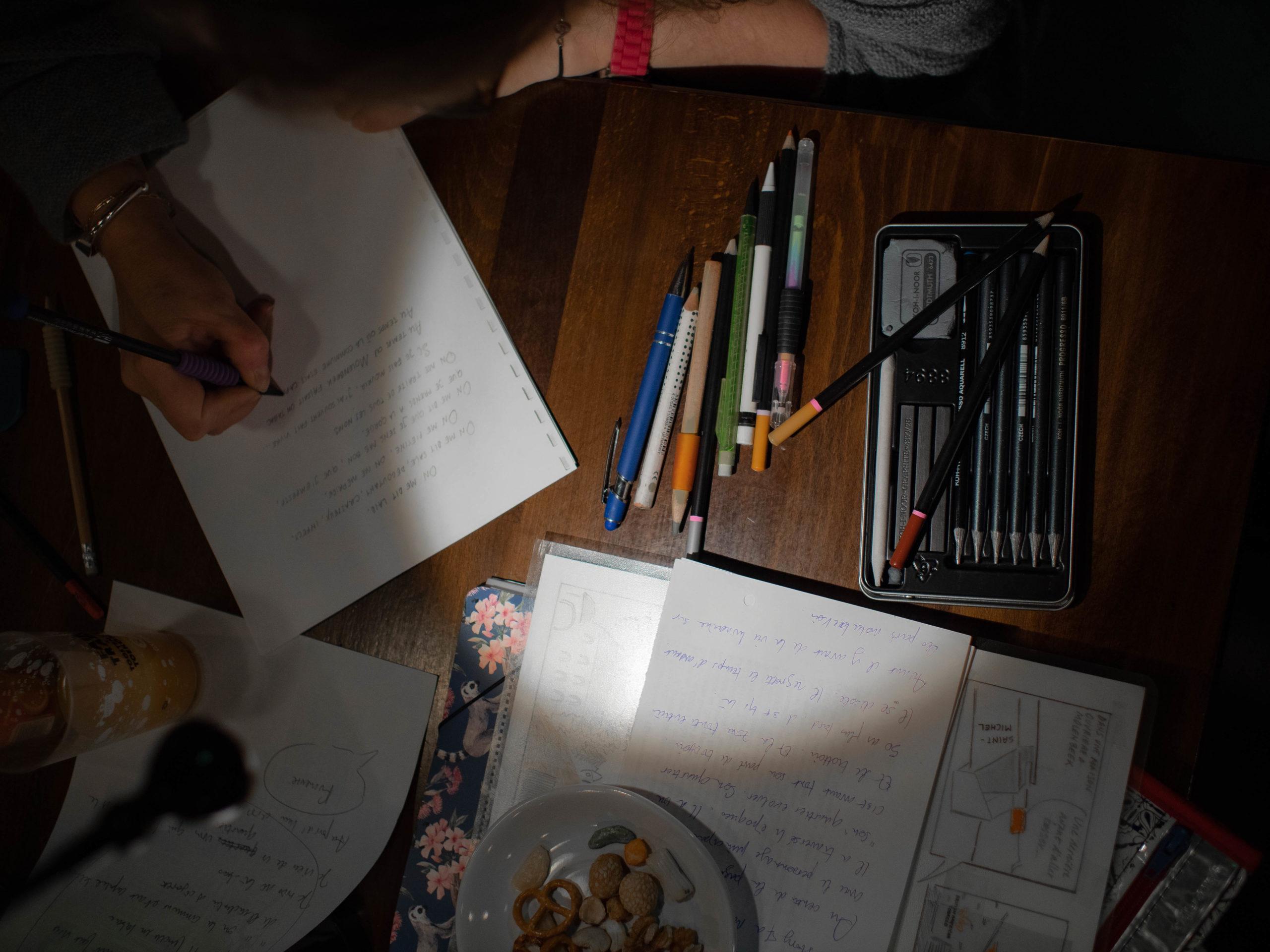 Vue en plongée sur les outils de l'atelier BD : stylos, crayons divers, papiers et dessins...
