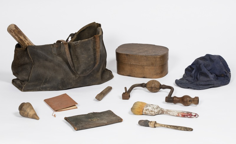 Musette en cuir d'un ouvrier plombier contenant une casquette,deux pinceaux, un burin en bois,un vilebrequin en bois et acier, une toupie ,un carnet, une pochette, un manche en bois et une boîte à tartines en bois.