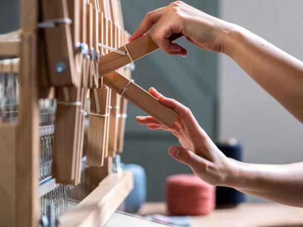 Des mains actionnent un métier à tisser.