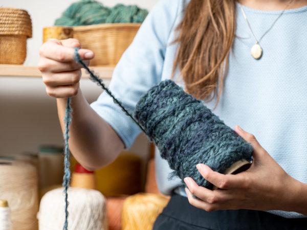La designer textile Saskia déroule un fil de laine bleu-gris.