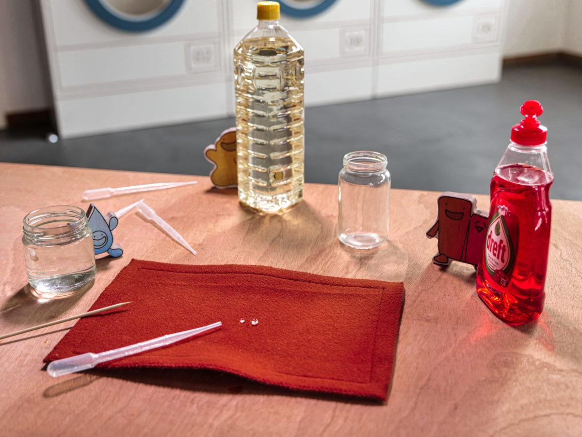 Kit pédagogique sur la lessive : expérience qui vise à expliquer l'interaction entre l'eau, la graisse et le savon.