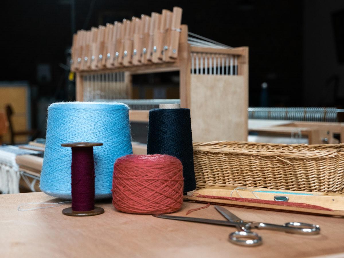 paire de ciseaux, bobines de fils et métier à tisser.