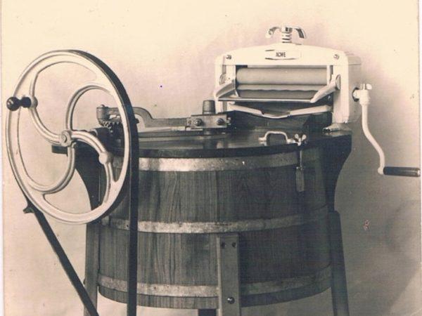 Ancienne photo d'une machine à laver avec moteur électrique et essoreuse.