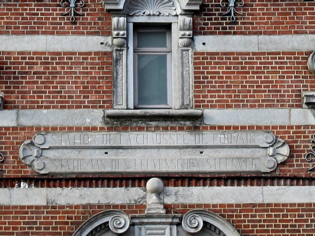 """Cartouche en pierre sur une façade avec l'inscription """"Station de la chaussée de Louvain"""""""