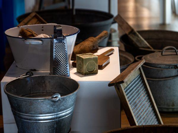 d'anciens ustensils pour la lessive - seau, cuve, planche à laver, savon et battoir - sont présentés dans une exposition.