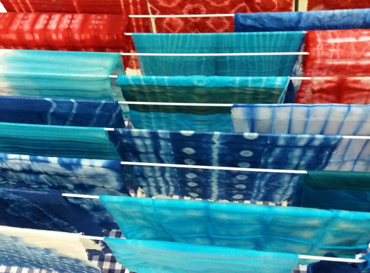 des tissus teint à la main sèchent sur un étendoir.